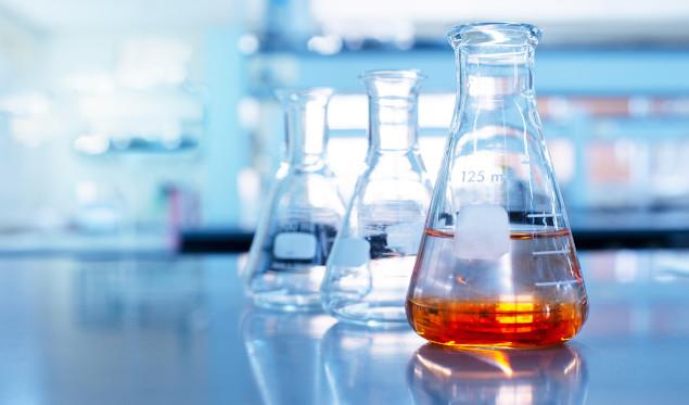orange solution in science glass flask in blue chemistry school laboratory background